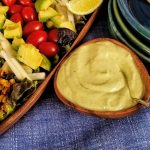Avocado dressing in wood bowl close up