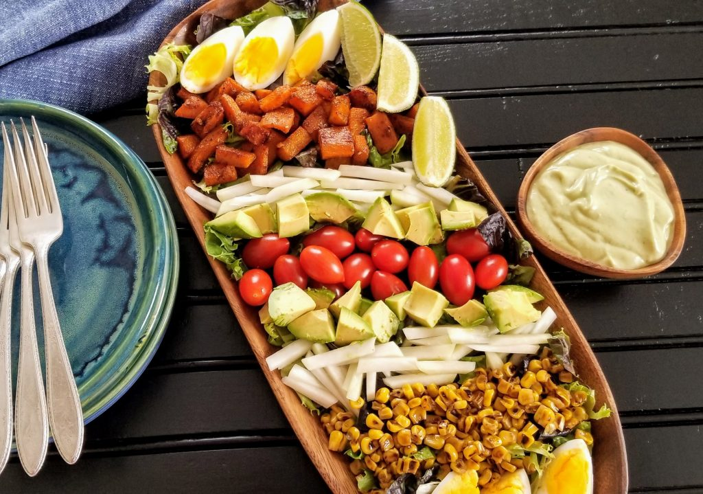 Avocado dressing in bowl alongside composed salad