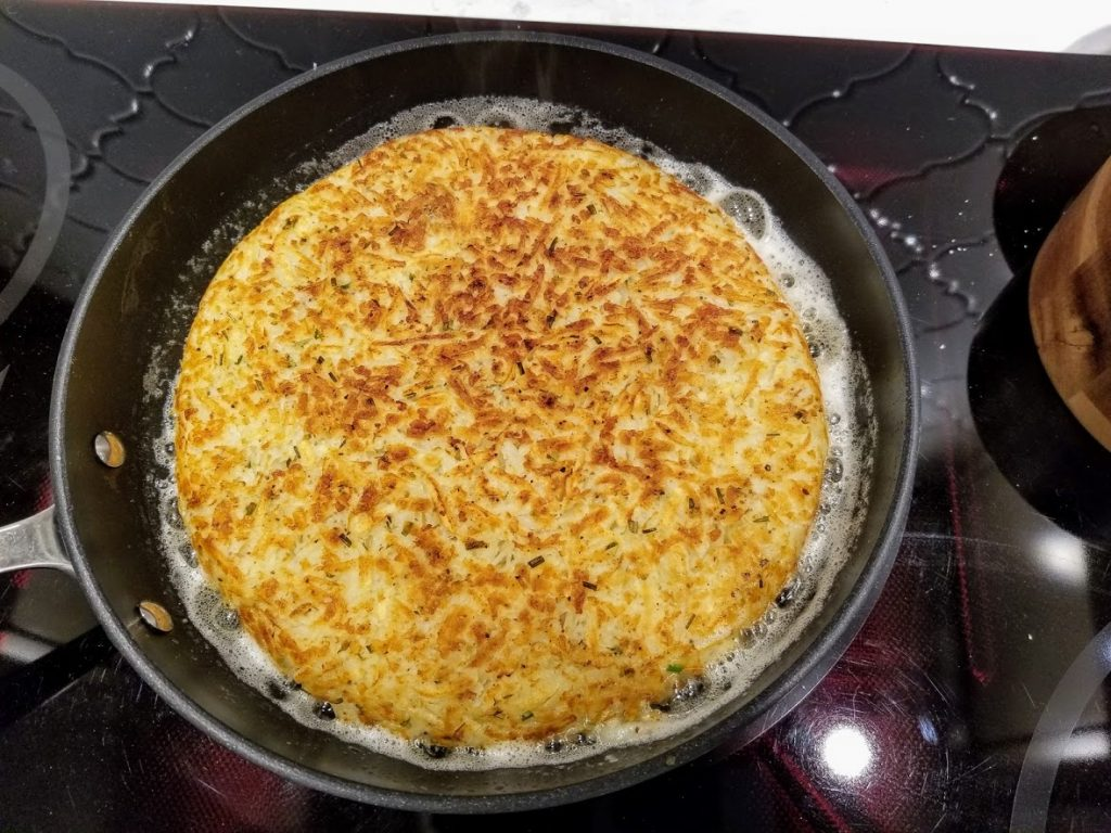 flipped crispy hash browns in skillet