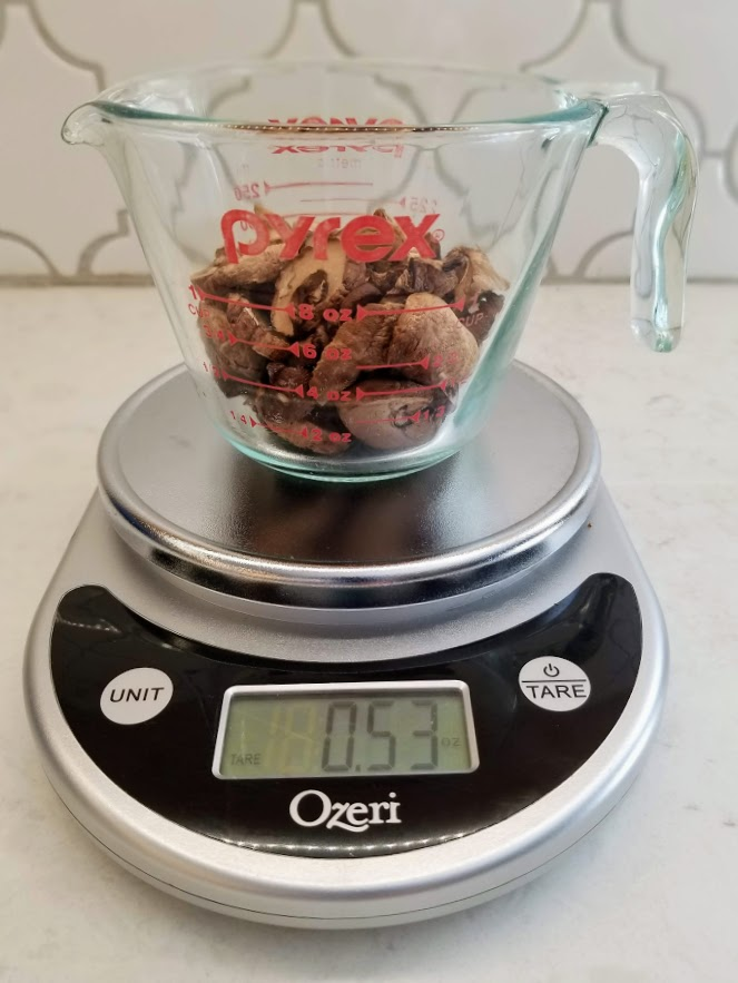 dried mushrooms in measuring cup on scale