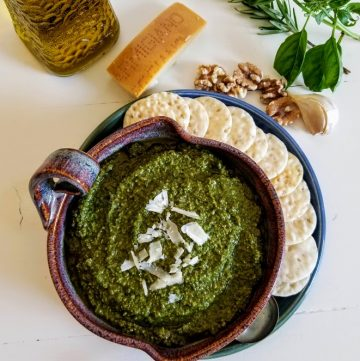 Basil pesto in bowl with crackers