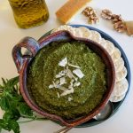Pesto in bowl with crackers and herbs on side