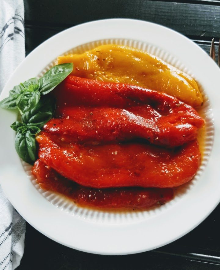 marinated roasted red peppers on a white plate with basil garnish