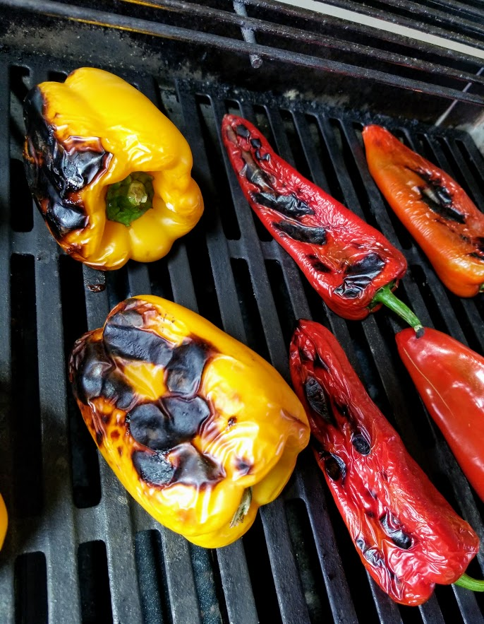 yellow and red peppers on a gas grill