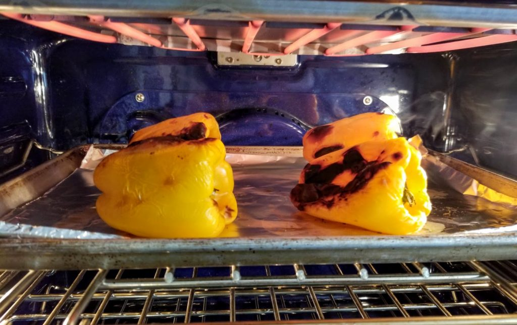 yellow peppers roasting under a broiler in oven