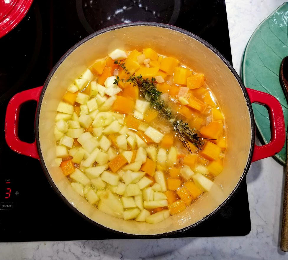 squash, apple and thyme in soup pot with broth
