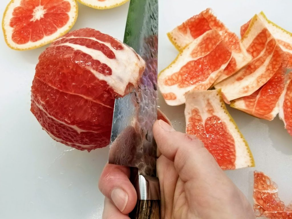 cutting away bits of pith from the grapefruit