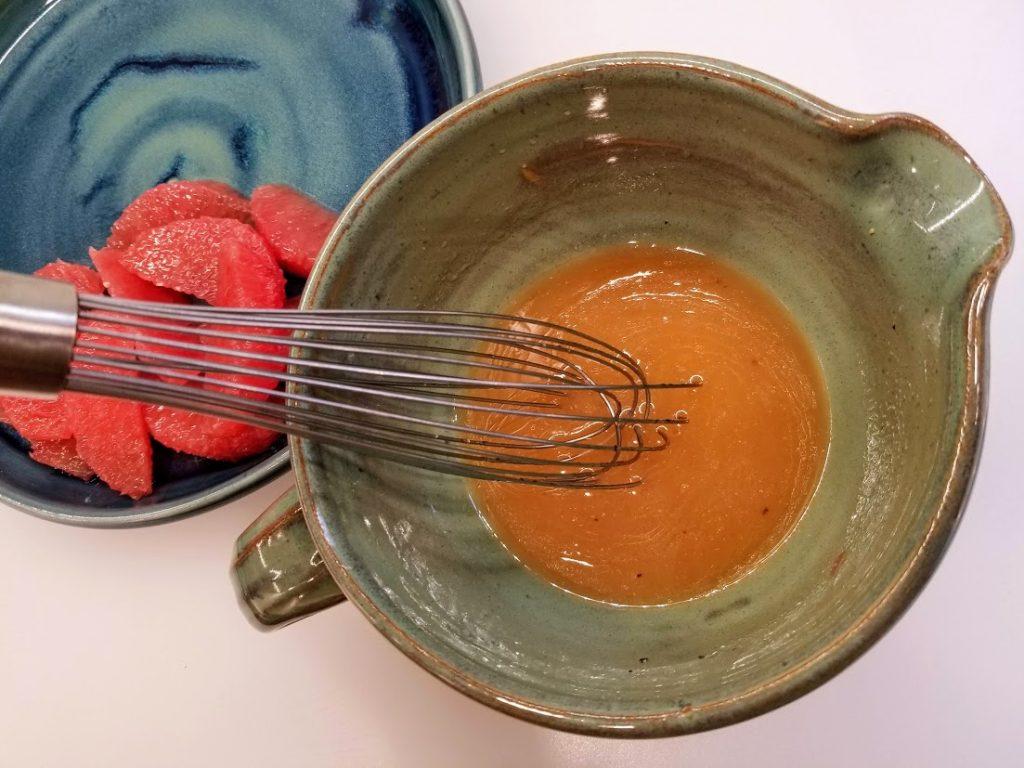 whisking fresh grapefruit vinaigrette in small bowl