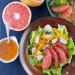 Grapefruit salad in bowl with dressing in a cup and halved grapefruit on the side