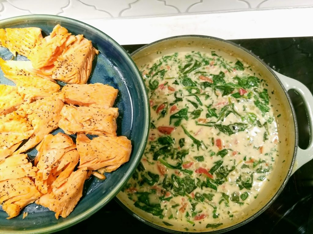 salmon being added to skillet of sauce