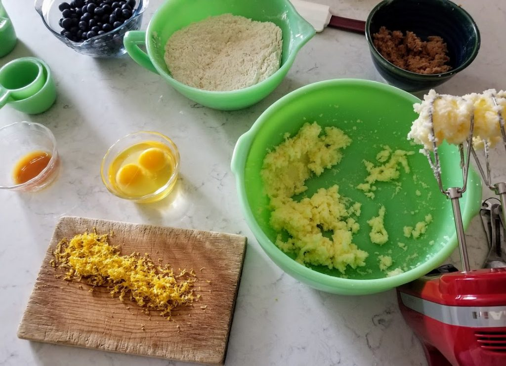 creamed butter and sugar in bowl, flour and eggs ready for mixing in