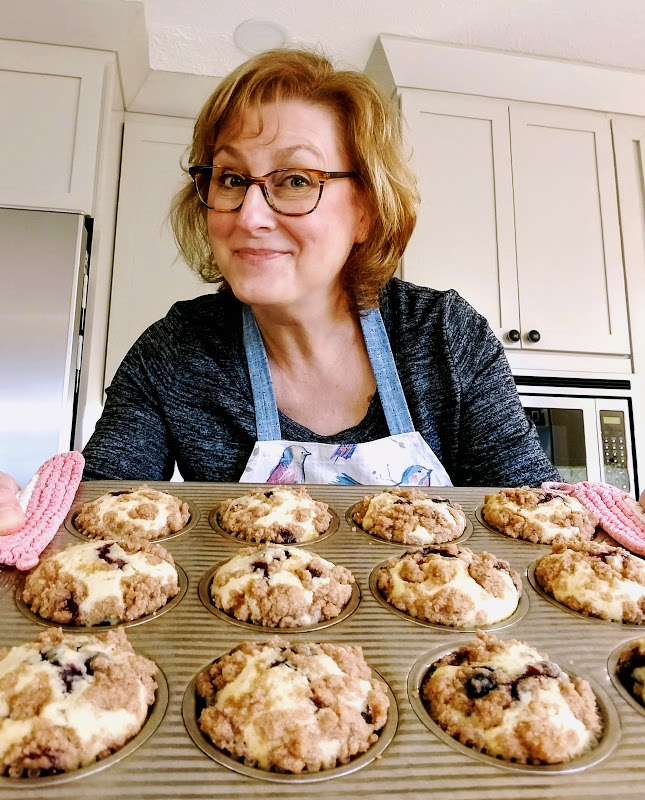 Donna holding tin full of baked muffins