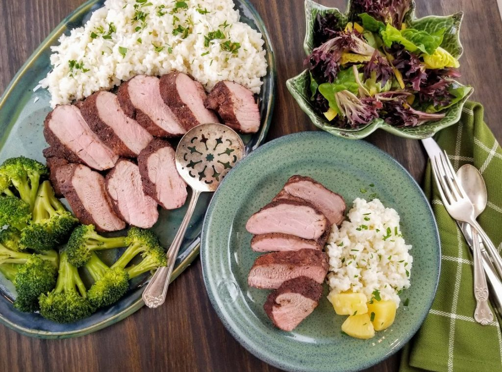 pork tenderloin sliced on latter and plated with rice