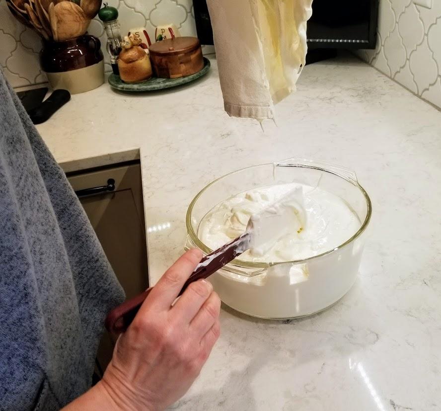 Holding towel above bowl of yogurt, scraping excess from towel