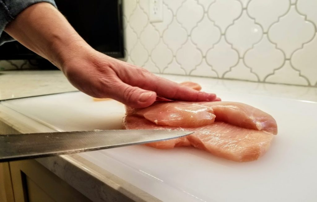 knife cutting completely through chicken breast thickness