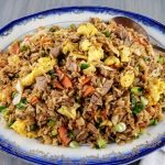 Leftover pork fried rice on a blue rimmed platter