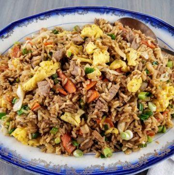Leftover pork fried rice on a blue rimmed platter