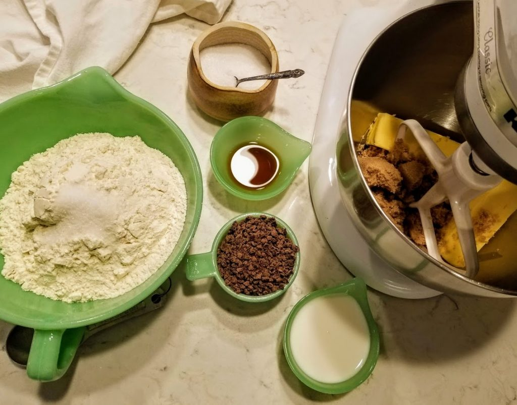 prep for cookie making laid out in green bowls: dry ingredients stirred together, vanilla, milk, chopped chocolate chips and mixer bowl holding the margarine and sugar