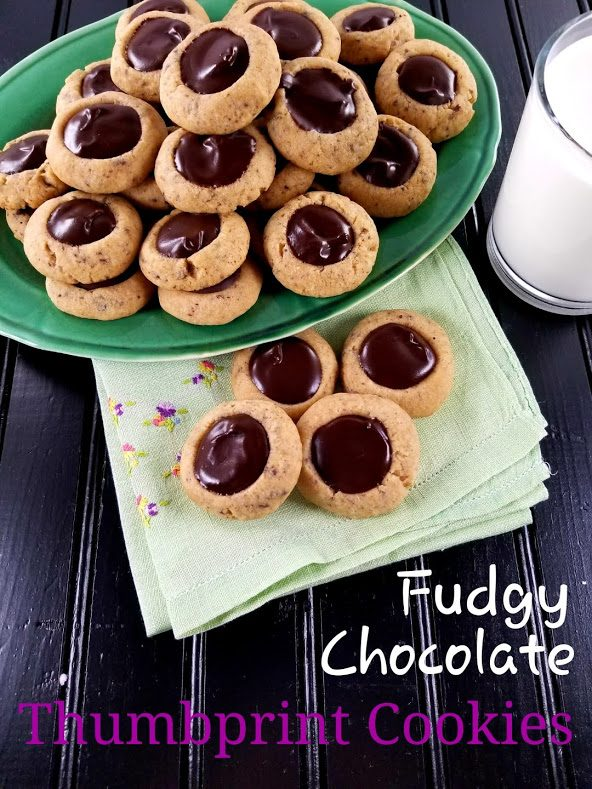 """green plate of chocolate thumbprint cookies with 4 cookies on a green napkin. Text """"Fudgy Chocolate Thumbprint Cookies"""" across the bottom."""