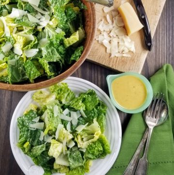 wooden bowl and white plate of salad with dressing in a green cup and Parmesan and knife on a small cutting board