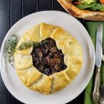 Mushroom, leek and bacon galette on white plate with knife and fork on a green napkin