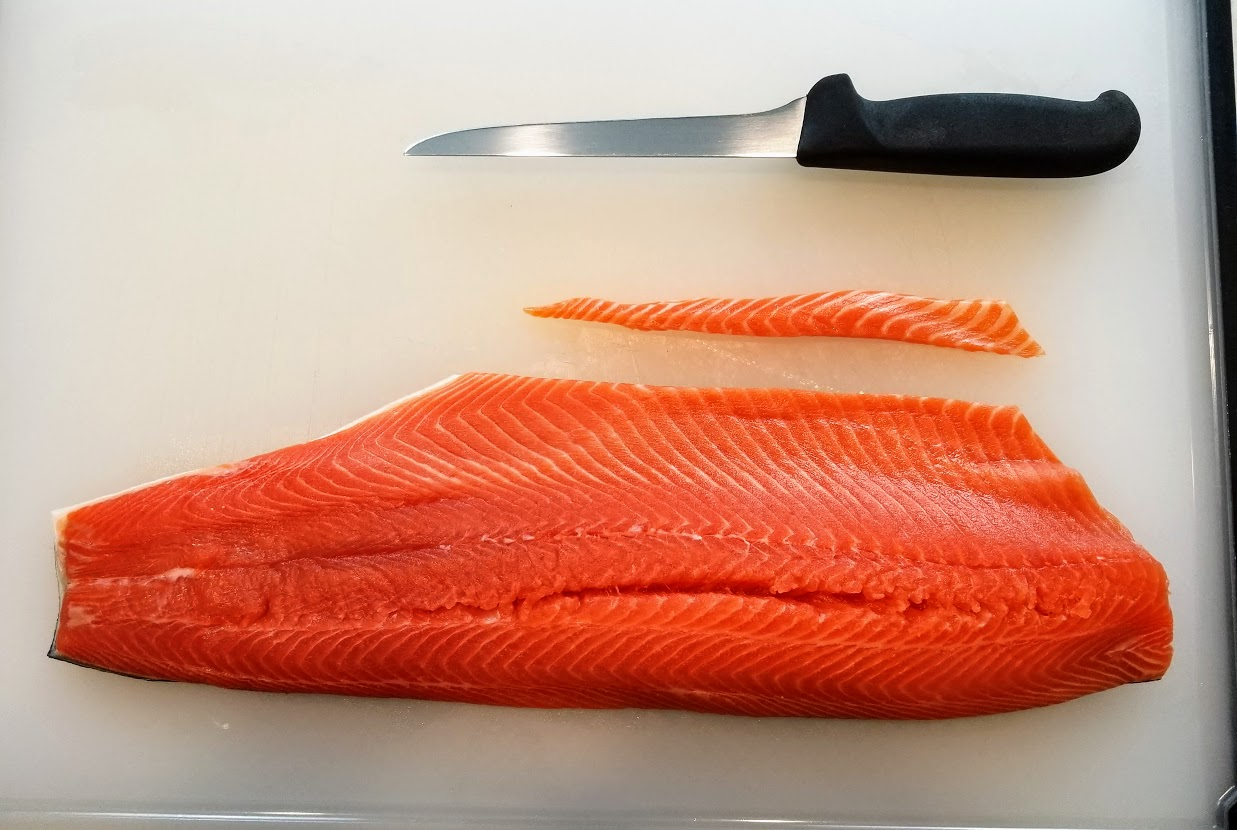 salmon fillet with skin on, but trimmed of thin edge. Boning knife lying above.