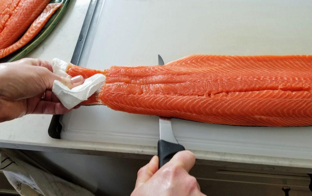 cutting off salmon skin, 1/3 way through
