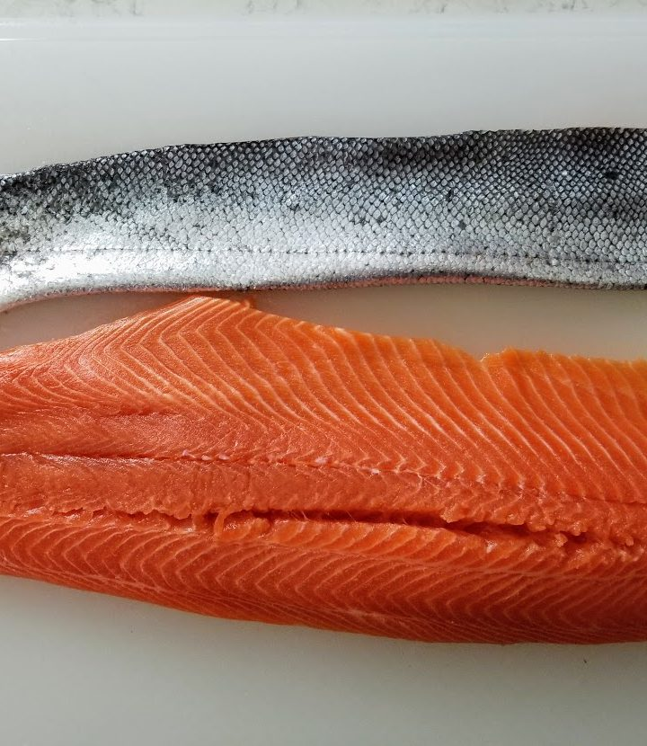 salmon lying on board with skin lying above it