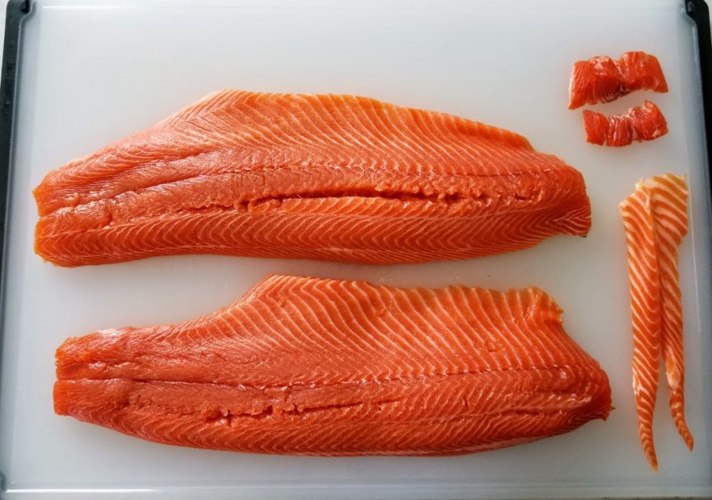 two skinned salmon fillets on board, plus bits from tail and thin trimmed edge