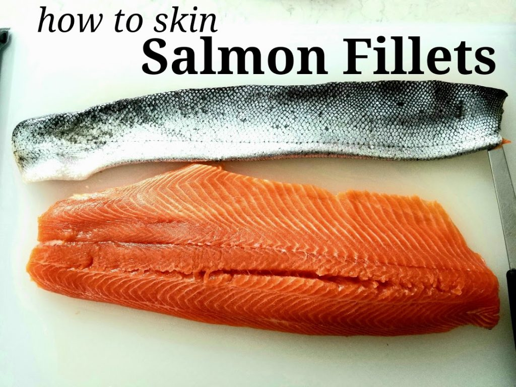 skinned salmon lying on white cutting board with removed skin lying above it. Overlayed text How To Skin Salmon Fillets above.