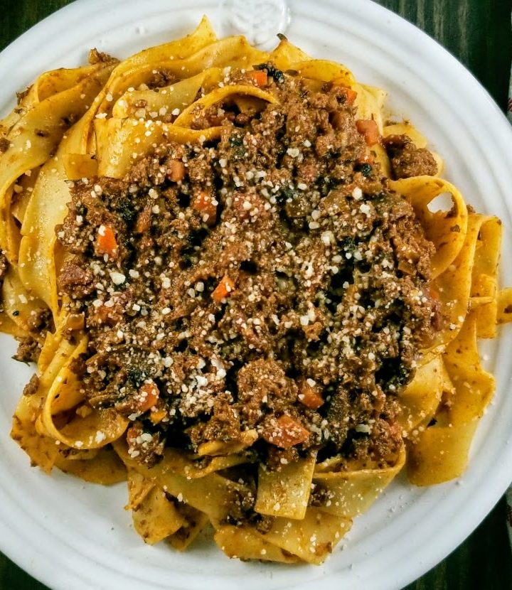 classic venison bolognese with pappardelle on a white plate
