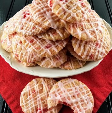 White platter of old fashioned cherry cookies, two of them on a red napkin.