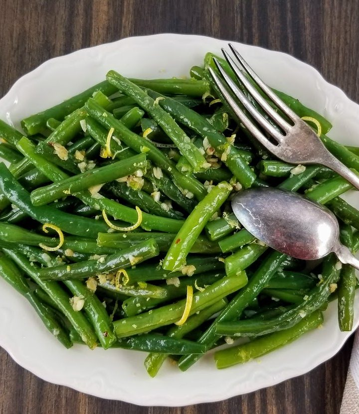 Lemon Garlic Green Beans on a white platter with a spoon and fork resting on the rim.