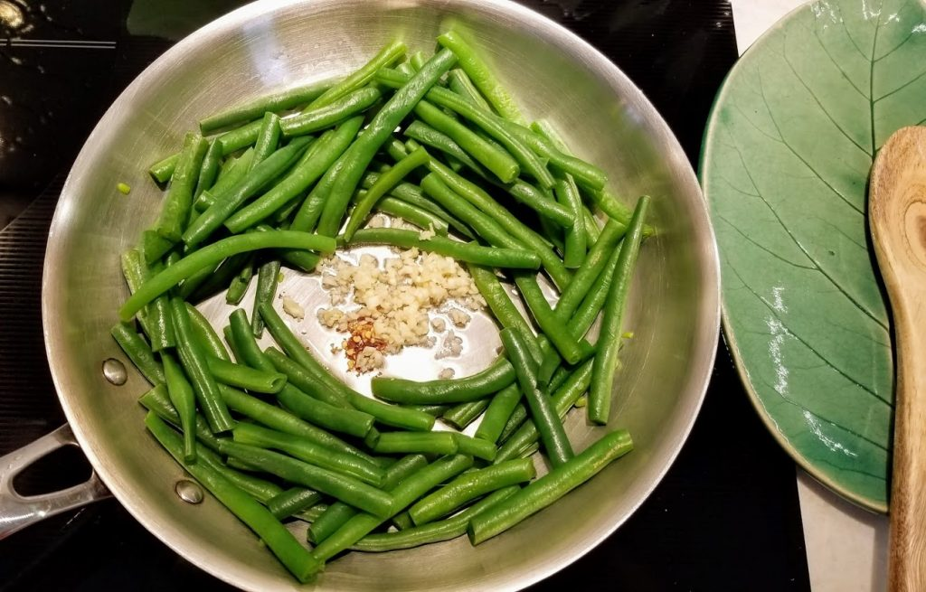 Steamed beans in skillet. Clear spot made in the center with garlic and red pepper added there with olive oil.