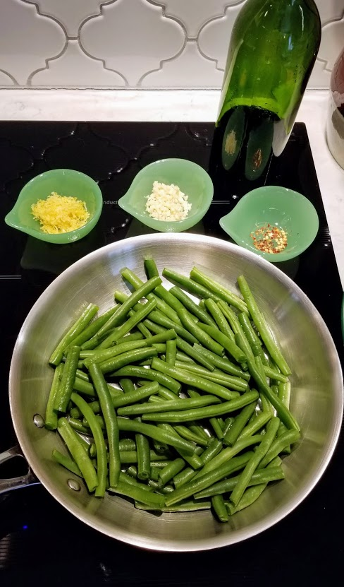 Green beans in skillet with small green dishes containing red pepper flakes, lemon zest and garlic around the skillet. Green bottle of olive oil at the top.